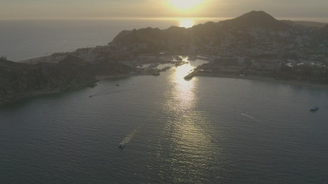 Boats and motorboats sailing along a coastline during sunset
