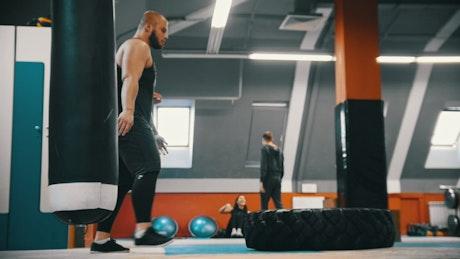 Bodybuilder flips a tire on the gym floor