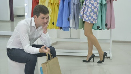 Bored man waits for girlfriend shopping clothes