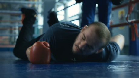 Boxer falling down into the ring floor
