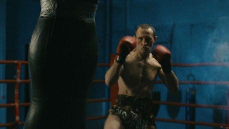 Boxer training hard with punching bag