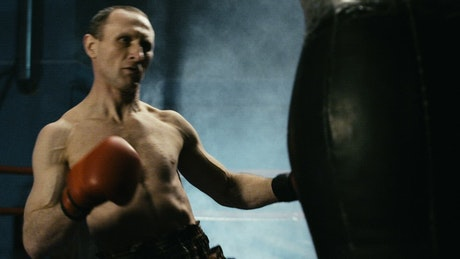 Boxer training hard with the punch bag