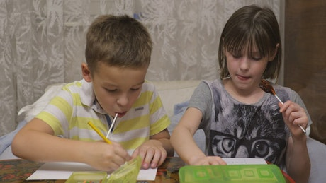 Boy and girl eating candy while drawing