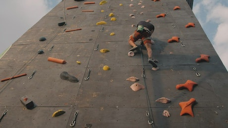 Boy climbing to the top of a mountaineering wall