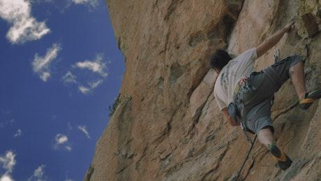Boy climbing up a rocky mountain