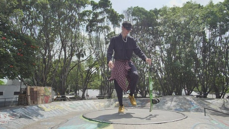 Boy doing a pirouette with a skateboard in a park