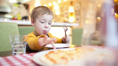 Boy eating breakfast in a cafe