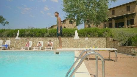 Boy entering the pool, side tracking shot