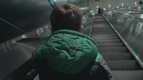 Boy heading up an escalator