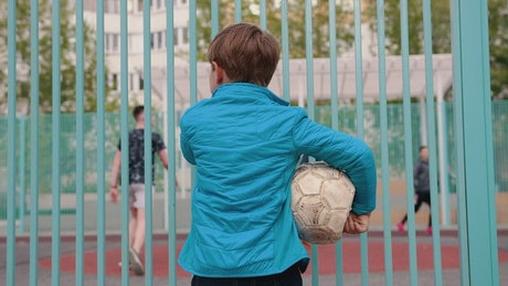 Boy holding deflated ball  watching other kids playing football