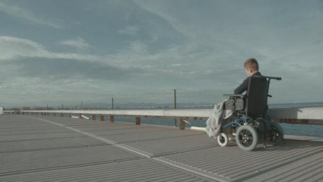 Boy in a wheelchair heading over a bridge
