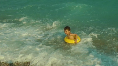 Boy in the seashore with a floaty