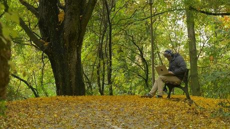 Boy keeps his things and retires in a park in autumn