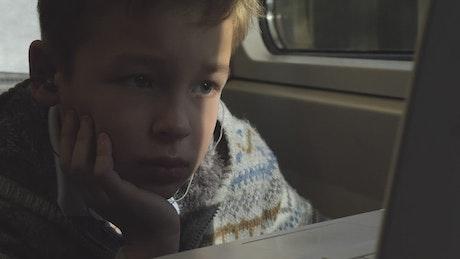 Boy listening to music on a train