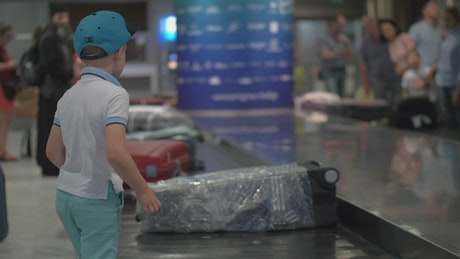 Boy looking for his bag at an airport