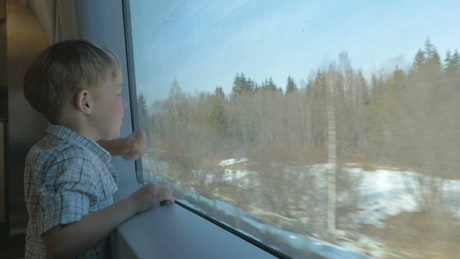 Boy looking out of a train window