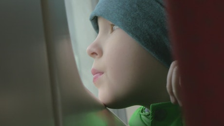 Boy looking out of a tram window