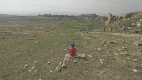Boy looking out over city ruins