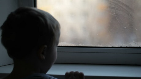 Boy looking through a misted window