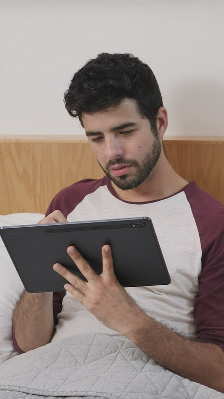 Boy lying concentrated with a tablet before sleeping
