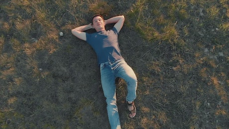 Boy lying outdoors, top zoom out aerial shot