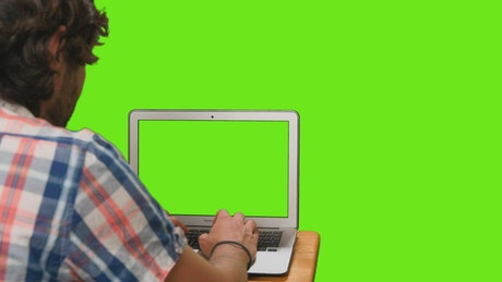Boy on his computer with green screen on a chroma background