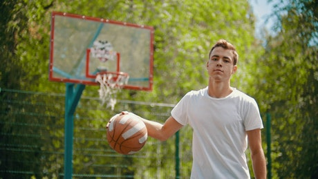 Boy playing basketball takes the shot and scores