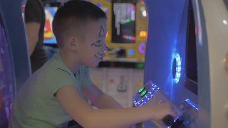 Boy playing on an arcade machine