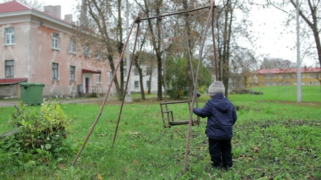 Boy playing on an old swing