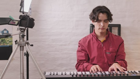 Boy playing piano being recorded