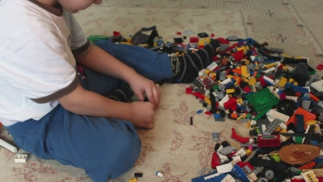 Boy playing with many Lego pieces on the floor