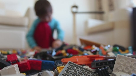 Boy pulling a lot of legos to the floor while