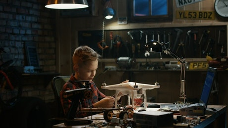 Boy repairing a drone in the garage