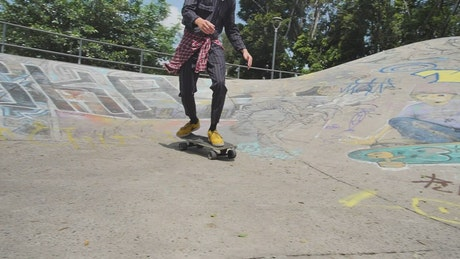 Boy skating with a skateboard in a park with ramps