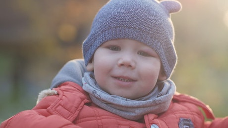 Boy smiling at the camera on a cold day