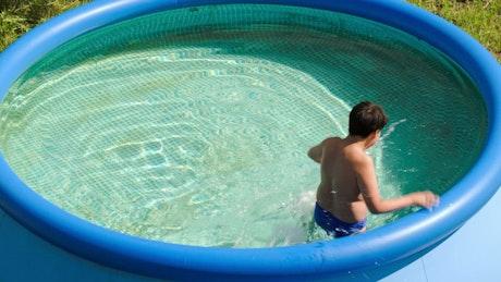 Boy splashing in a small pool