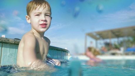 Boy splashing the camera with pool water