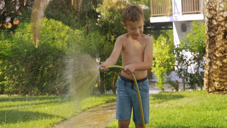 Boy spraying a garden hose