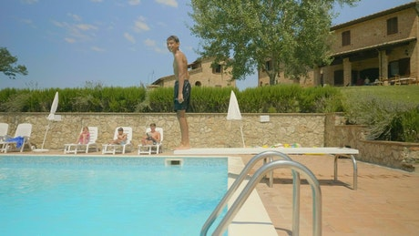 Boy swimming in an outdoor pool on a sunny day