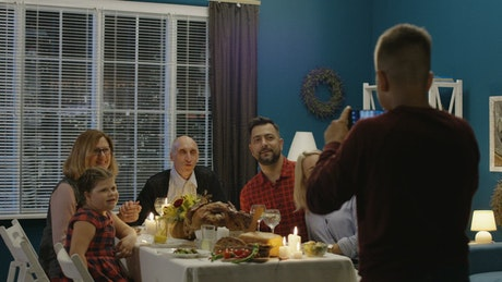 Boy takes a photo of family in thanksgiving dinner