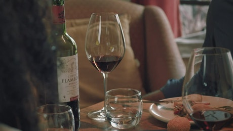 Boy takes his glass of wine during a dinner with a girl
