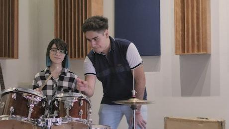Boy teaching a girl to play drums