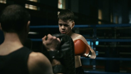 Boy training boxing on the ring