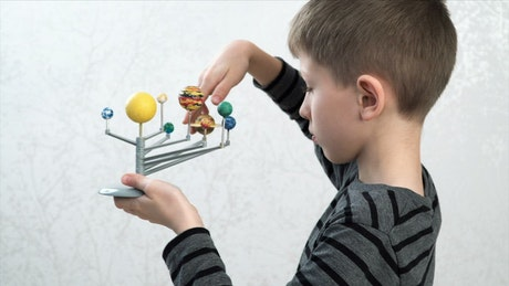 Boy with a model of the Solar System