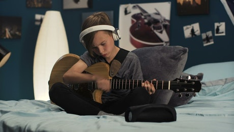 Boy with headphones playing the guitar in the room
