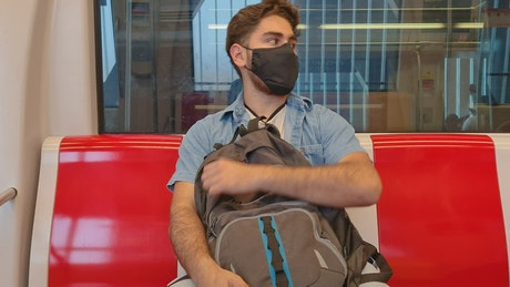 Boy with mask and backpack traveling by subway