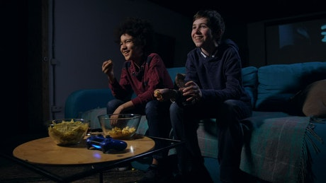 Boys laughing while watching TV
