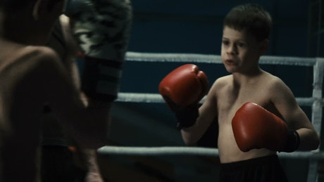 Boys training boxing with instructor
