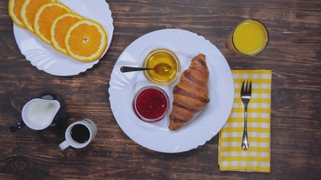 Breakfast at a table with bread, coffee and fruit