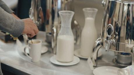 Breakfast bar or coffee bar with a woman preparing tea